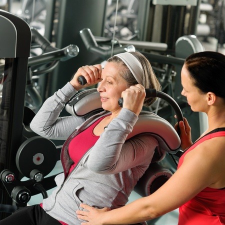 school gym: Senior woman at gym exercise with personal trainer on machine