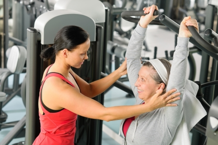 aide à la personne: Exercice femme senior sur la machine de Presse de l'épaule avec un entraîneur personnel