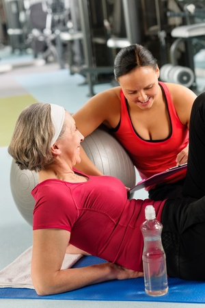 Fitness center senior woman relax on mat with personal trainer photo