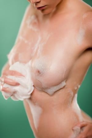 wet breast: Woman body using bath sponge on green