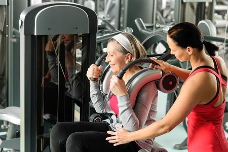 aide à la personne: Senior femme à l'exercice de gym avec un entraîneur personnel sur la machine
