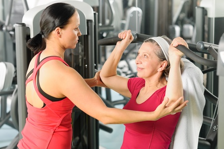 school gym: Personal trainer assist senior woman exercising on machine at gym