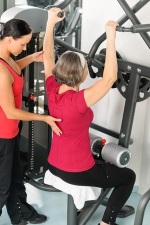 aide à la personne: Centre de fitness entraîneur personnel principal épaule exercice femme sur la machine Banque d'images