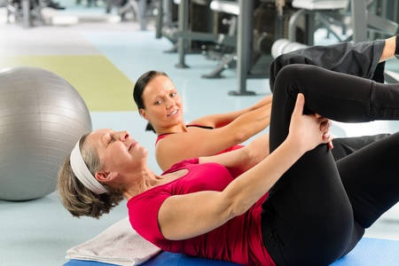 sit ups: Fitness center senior woman exercise sit ups with personal trainer