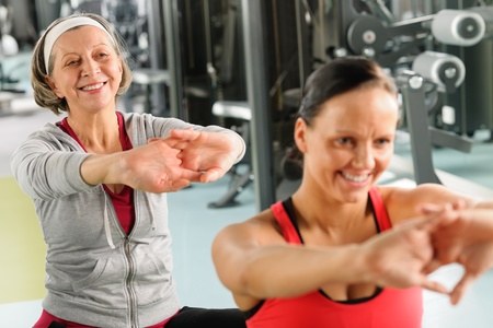 fitness trainer: Senior woman with personal fitness trainer stretch out at gym Stock Photo