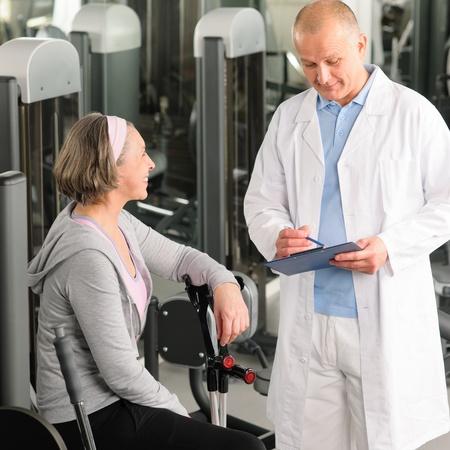 Fysiotherapeut man te assisteren actieve senior vrouw oefening op sportschool