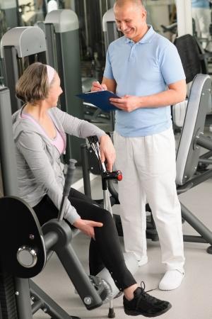 física: Hombre fisioterapeuta ayudar a la mujer mayor ejercicio activo en el gimnasio