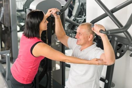 aide à la personne: Centre de fitness assistance entraîneur personnel exercice homme sur la machine de l'épaule