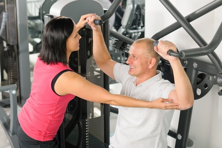 Fitness center personal trainer assist man exercise shoulder on machine photo