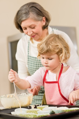 Woman and little girl make cupcakes together fill baking form Stock Photo - 12757474