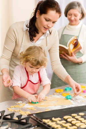 Little girl with mother cutting out cookies in kitchen photo
