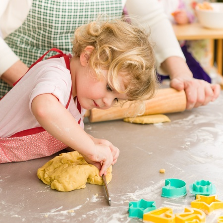 Little girl cutting out dough for cookies cute blond child Stock Photo - 12757420