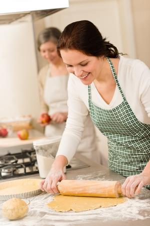 Happy woman making dough for apple pie grandmother peeling apples Stock Photo - 12757499