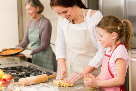 mere cuisine: Trois femmes de cuisson de pommes grand-m�re tartes, m�re et fille Banque d'images
