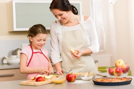 niños cocinando: Sonriendo madre e hija de corte las manzanas para hornear un pastel de Foto de archivo