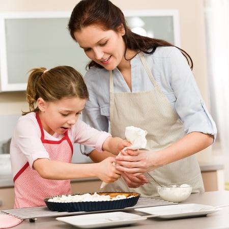 ni�os cocinando: Madre e hija decorar pastel con crema batida