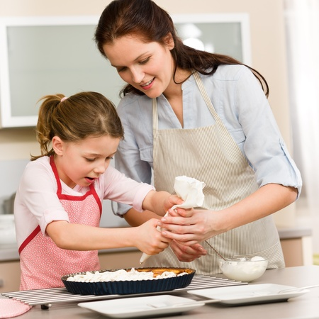 Mother and daughter decorating pie with whipped cream photo