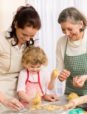 granddaughter: Little girl with mother cutting out cookies in kitchen Stock Photo