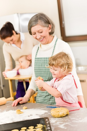 Grandmother with little girl prepare dough for baking in kitchen photo