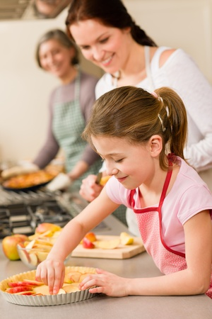 girl apple: Young girl prepare apple tart baking with mother and grandmother