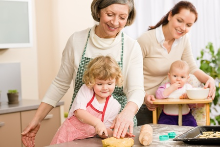 grandmother grandchild: Grandmother with little girl prepare dough for baking in kitchen