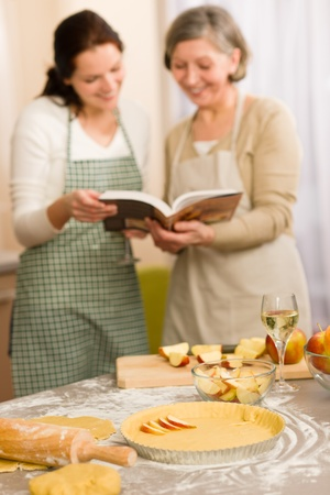 Apple pie recipe two women looking in cookbook happy baking photo