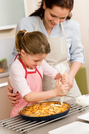Mother and daughter decorating apple pie with whipped cream Stock Photo - 12758025