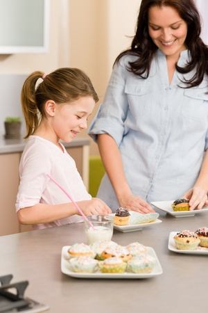 Little girl taste sprinkles cupcakes with mum happy at home Stock Photo - 12757934