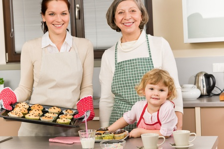 Family women baking cupcakes in kitchen grandmother, mother and granddaughter photo