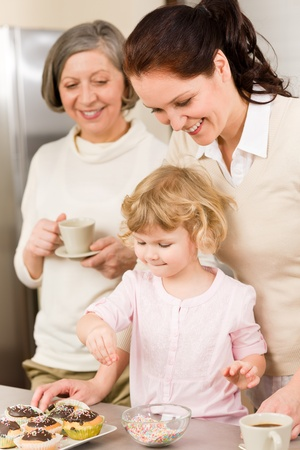 Mother and daughter decorating cupcakes sprinkles happy together at home Stock Photo - 12758058