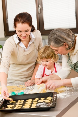 Happy little girl rolling out dough with mum and grandmother Stock Photo - 12758141