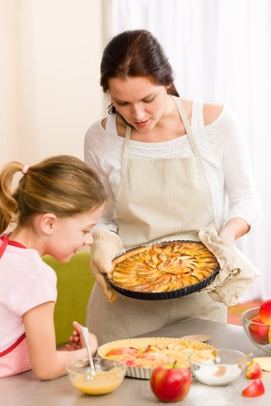 apple tart: Apple pie mother and daughter baking together happy at home