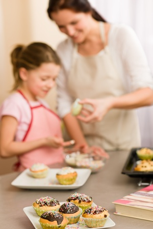 Little girl taste sprinkles decorating cupcakes with mother at home Stock Photo - 12758015