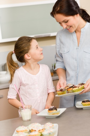 Little girl taste baked cupcakes with mum happy at home photo
