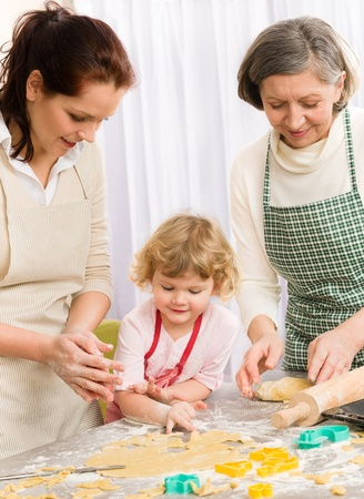 Little girl with mother cutting out cookies in kitchen Stock Photo - 12758223