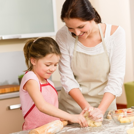 little dough: Mother and daughter prepare dough baking apple cake happy together Stock Photo