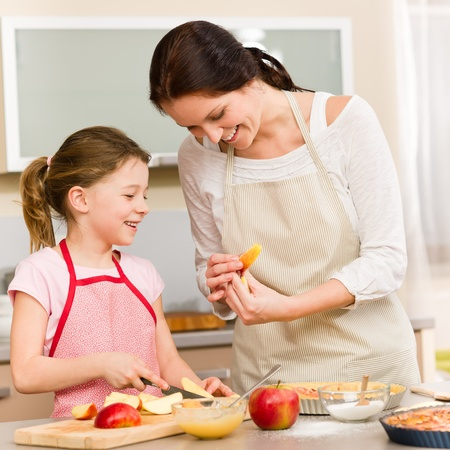 Smiling mother and daughter cutting apples for baking a pie Stock Photo - 12758177