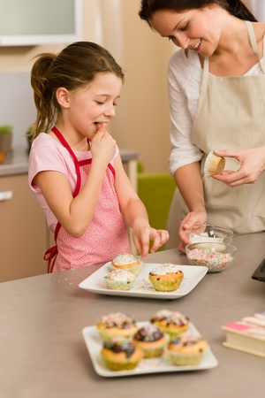 Little girl taste sprinkles decorating cupcakes with mother at home photo