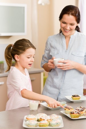 Little girl pointing cupcake to her mother happy at home photo