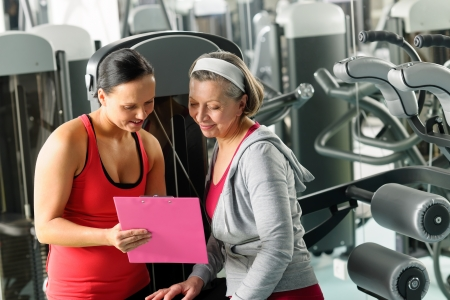 aide à la personne: Senior femme avec carte formateur exercice personnel à la recherche au gymnase