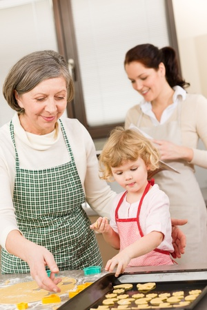 Little girl with grandmother baking cookies put on tray Stock Photo - 12758262
