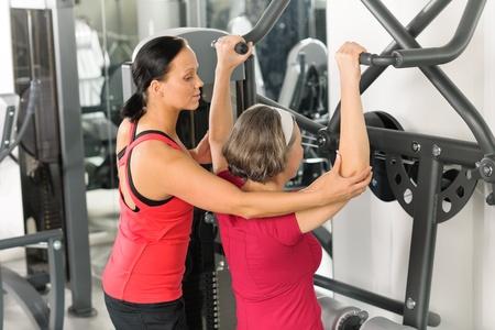 aide à la personne: Senior femme à l'épaule de remise en forme centre d'exercice avec un entraîneur personnel