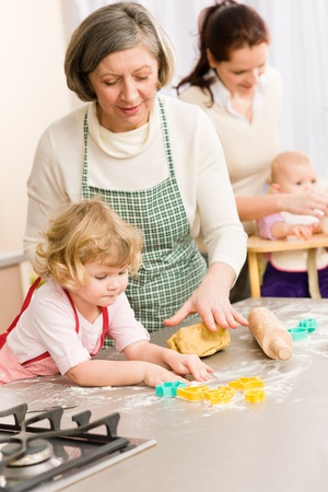 Grandmother with little girl prepare dough for baking cookies photo