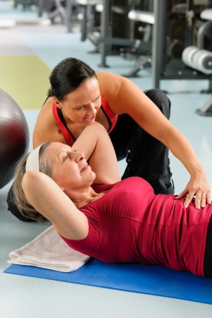 Fitness center senior woman exercise with personal trainer on mat photo