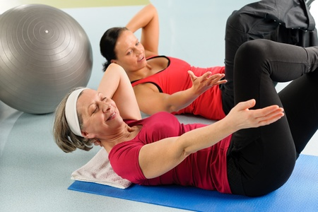 trainer: Fitness center senior woman exercise sit ups with personal trainer