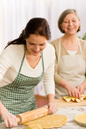 Happy woman making dough for apple pie grandmother drink wine Stock Photo - 12758247