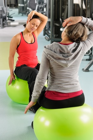 Fitness center senior woman with trainer stretching on swiss ball photo