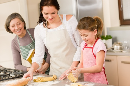 grandmas: Three generation of happy women baking in kitchen prepare dough