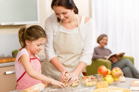 Mother and daughter making apple pie together grandmother check recipe Stock Photo - 12758253