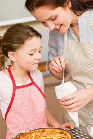 Mother and daughter decorating apple pie with sugar icing Stock Photo - 12756927